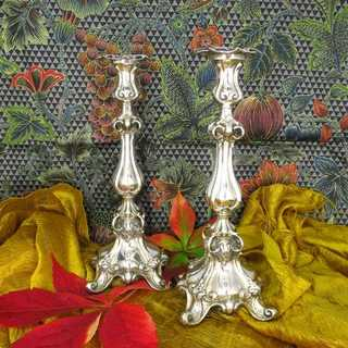 A pair of reich decorated silver candlesticks