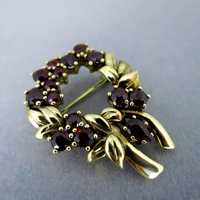 Beautiful wreath brooch in gold with deep red bohemian...