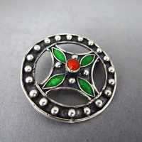 Round open worked silver brooch with red coral and green...