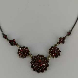 Magnificent necklace in a floral design set with deep red garnet